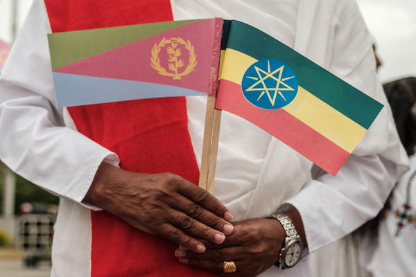 A man holds national flags of Eritrea (left) and Ethiopia as he waits for the arrival of Eritrea's president at the airport in Gondar, nothern Ethiopia, in November.