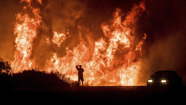 A motorist on Highway 101 watches flames from the Thomas Fire leap above the roadway north of Ventura on Dec. 6, 2017.