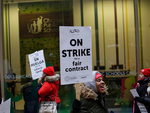 Educators from the Acero charter school network hold signs as they protest during a strike outside Chicago Public Schools headquarters.