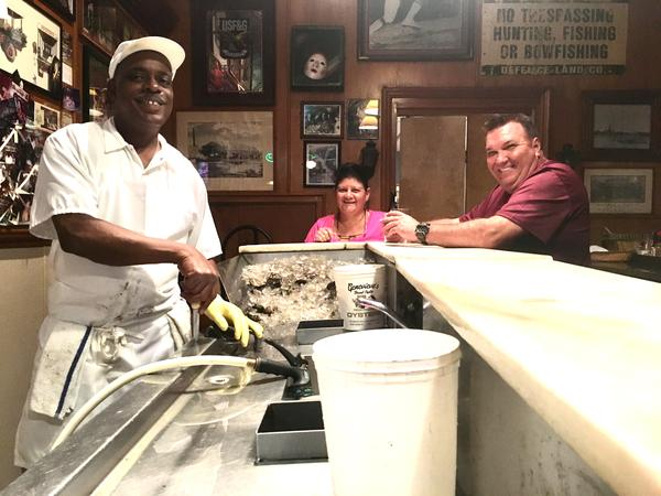 "Oyster shucker Thomas ""Uptown T"" Stewart poses with oyster bar regulars Paula and Brent Coussou at Pascal's Manale."