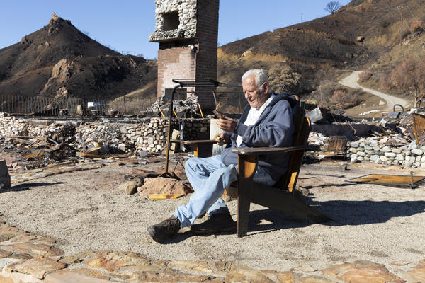 Holding a cigar, Gary Jones sits where his house once stood, in a wooden porch chair that somehow wasn't destroyed. Jones lost three of his five dogs in the flames and came back the next day to bury them. His horse was found alive up the hill and is recovering from burns.