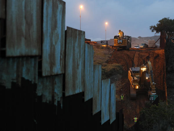 Contractors work to reinforce a section of the U.S. border wall in San Diego where scores of Central American migrants have crossed illegally in recent weeks, shot through the fence from Tijuana, Mexico.