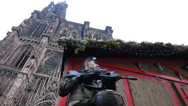 A French soldier stands guard at the Christmas market in Strasbourg, in front of the city's cathedral, as police conduct a search for a man suspected of opening fire on a crowd the night before.