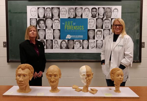 """St. Petersburg Police cold case investigator Brenda Stevenson, left, and USF forensic anthropologist Erin Kimmerle are surrounded by some of the work from this year's """"Art of Forensics"""" event."""