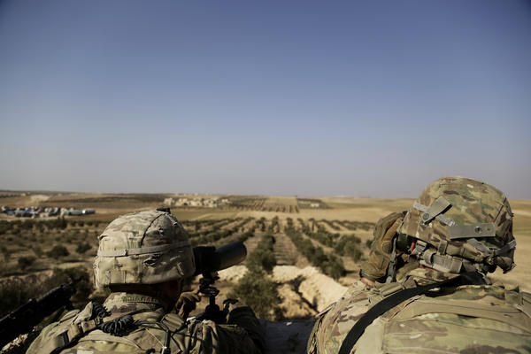 American troops look toward the border with Turkey from a small outpost near the town of Manbij, northern Syria, in February.