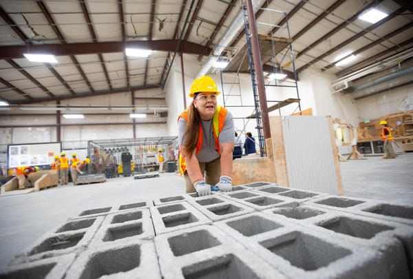 Crystal Lansdale carrying concrete blocks during a practice at a TRAC workshop in the Washington Corrections Center for Women in Gig Harbor, Wash.
