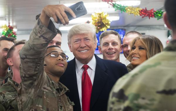 President Trump and first lady Melania Trump greet members of the U.S. military during an unannounced trip to al-Asad Air Base in Iraq on Wednesday.