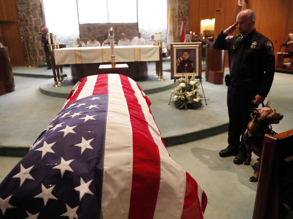 As of Dec. 27, this year 144 federal, state and local law enforcement officers have died in the line of duty — a rise from the 129 officers killed in 2017. Here, wounded Dekalb County Police K9 Indi stands by his handler's side during a funeral service for Edgar Flores on Dec. 18 in Georgia.