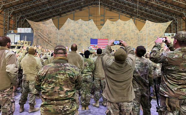 U.S. military personnel listen to President Trump speak at Al Asad Air Base on Wednesday.
