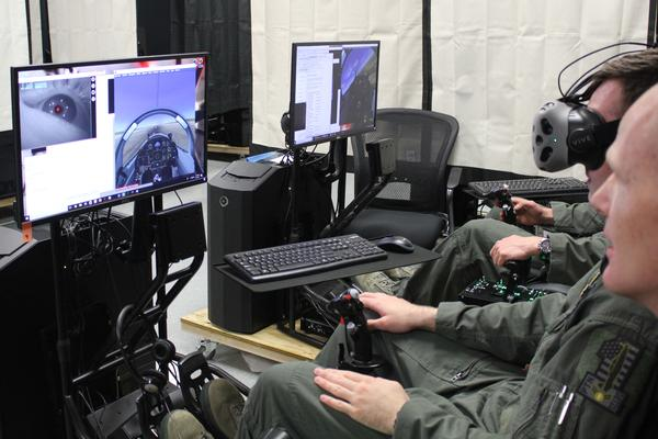 Airman 1st Class Jack Pepper (with goggles) attempts a maneuver on a simulator while Lt. Col. Paul Vicars looks on. Pepper is among the first participants in Pilot Training Next, which uses off-the-shelf virtual reality technology.