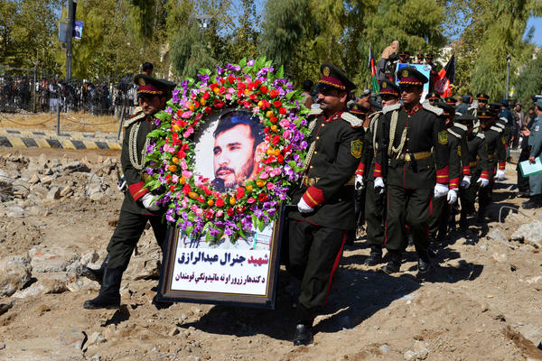 Guards of honor carry a photo of Brig. Gen. Abdul Raziq, Kandahar police chief, at his burial ceremony in Kandahar in October.
