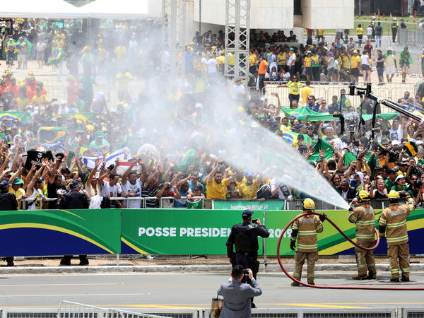 spray water to cool down supporters of Brazilian President-elect Jair Bolsonaro, as they gather to wait for his inauguration ceremony.