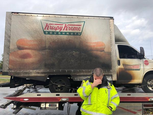 A Lexington, Ky., police officer poses, jokingly, in front of a charred Krispy Kreme truck Monday.