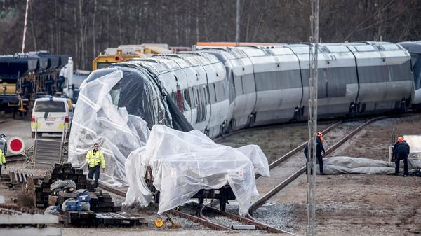 Investigators say it could be months before they present a final report on a passenger train's accident on a bridge in central Denmark. Here, the train is seen covered by plastic in Nyborg, on Funen island.