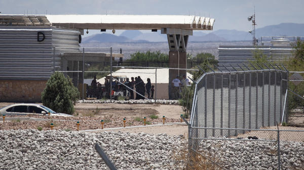 People wait outside the port of entry at Tornillo, Texas, in June 2018. Beyond them is one of the tents that were put up to house unaccompanied migrant children.