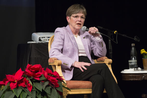 Gov.-elect Laura Kelly speaks at a Kansas News Service event in December. On Thursday, Kelly announced a new interim head of two state agencies, and called for a halt to recently awarded grants for private foster care contractors.