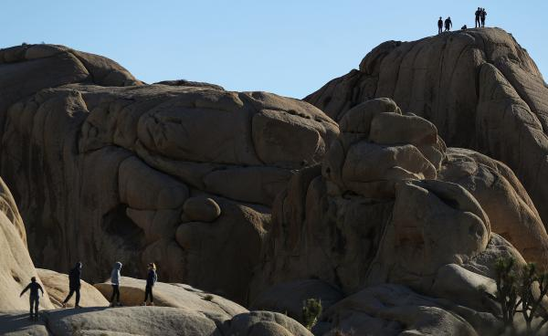 During the shutdown, visitors walk and stand atop rock formations at Joshua Tree National Park on Friday.