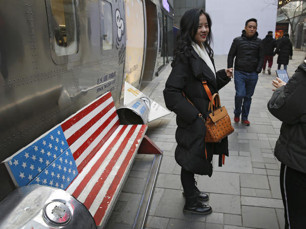 Chinese shoppers spend their time next to a bench painted with the U.S. flag at the capital city's popular shopping mall in Beijing. During trade talks this week, the two sides face potentially lengthy wrangling over technology and the future of their economic relationship.