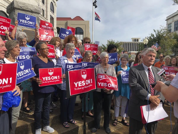 Supporters of Missouri's redistricting ballot measure hold signs behind former state Sen. Bob Johnson during a news conference in Jefferson City, Mo., in August.