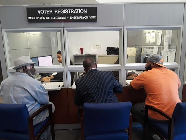 Several people affected by Amendment 4 register to vote at the Miami-Dade Department of Elections.