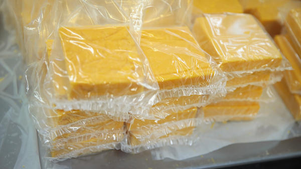 Cheese is packaged for sale at Widmer's Cheese Cellars in 2016 in Theresa, Wis. Record dairy production in the U.S. has produced a record surplus of cheese causing prices to drop.