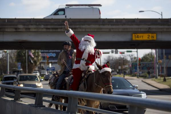 Sam Grey Horse (in Santa suit) and Nico Leophonte ride mules along East Cesar Chavez Street on Sunday.