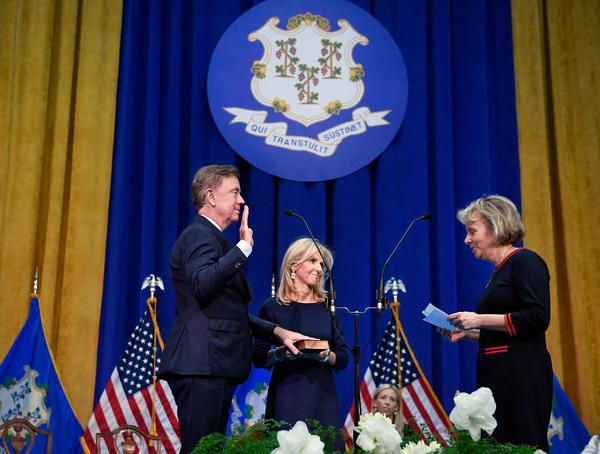 Ned Lamont takes the oath from former state Chief Justice Chase T. Rogers while his wife Annie holds the Bible.