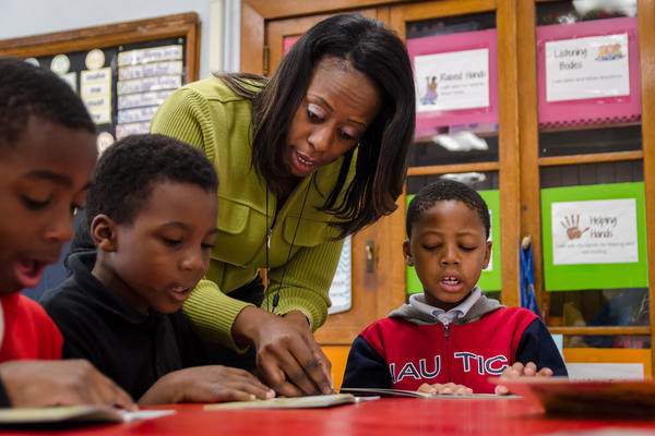 Iris Jackson works with first-graders at Patrick Henry Downtown Academy in St. Louis on a reading comprehension assignment in November. Jackson is a member of a new teacher residency program that's trying to reduce teacher turnover.