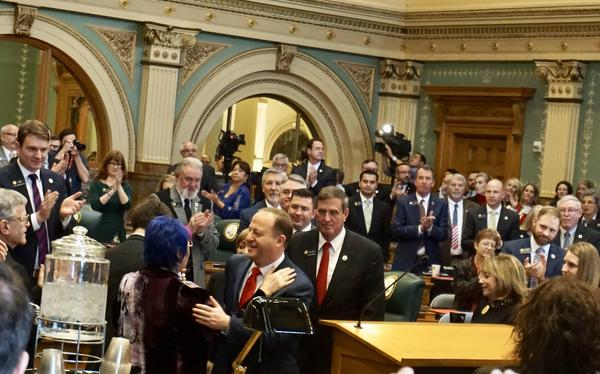 Gov. Polis is greeted on the House floor before giving his first State of the State address to lawmakers.
