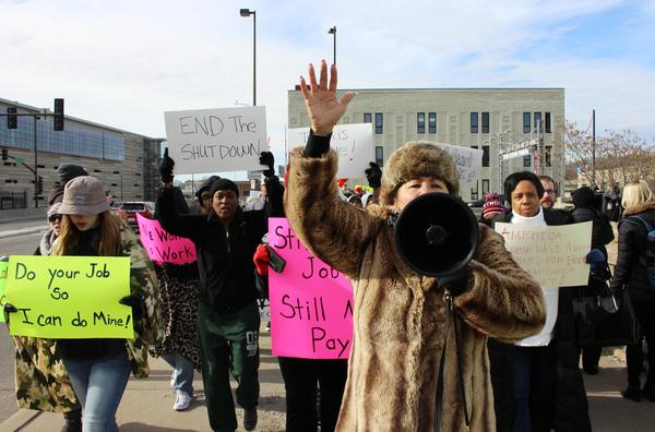 IRS employee Cita Mitchell led protesters on a march down the street Thursday at a rally against the government shutdown.
