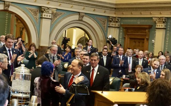 Colorado Gov. Jared Polis is embraced by his mother before his State of the State address on Thursday morning.