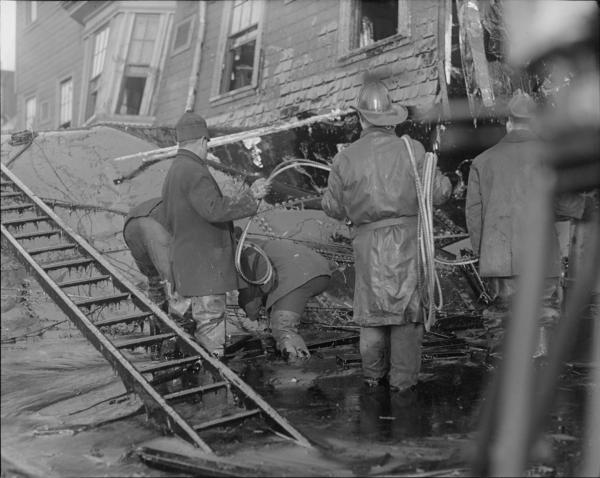 Firemen standing in thick molasses after the Boston Molasses Flood.