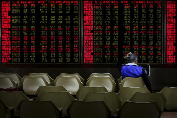 An investor monitors stock prices at a brokerage house in Beijing, Friday, Dec. 14, 2018, when Asian markets tumbled after China reported weaker-than-expected economic data, stirring up worries about the state of the world's second-largest economy. (Andy Wong/AP)