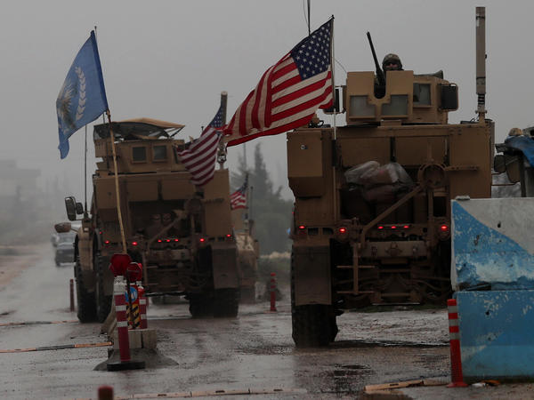 "The Pentagon has ""begun the process of our deliberate withdrawal from Syria,"" a military spokesman says. In this photo from Dec. 30, 2018, a line of U.S. military vehicles are seen at a checkpoint in northern Syria."