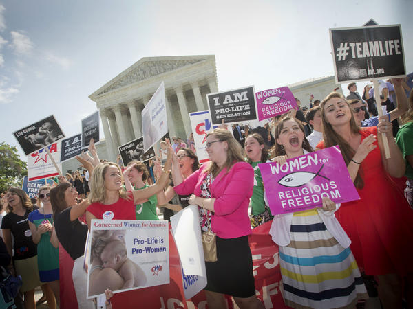 Demonstrators outside the U.S. Supreme Court in Washington, D.C., in 2014 react to hearing the court's decision on the Hobby Lobby birth control case.