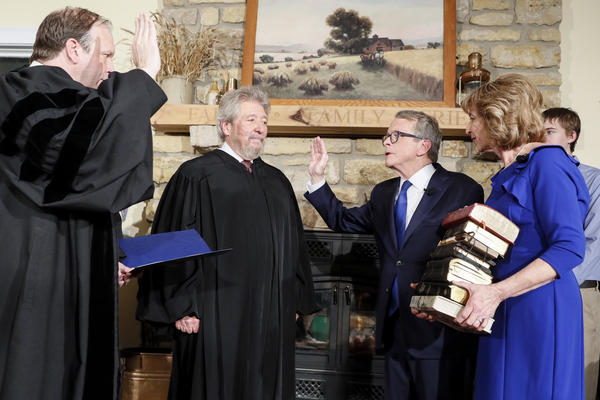 Gov. Mike DeWine takes the oath of office administered by his son and Ohio Supreme Court Justice Pat DeWine.