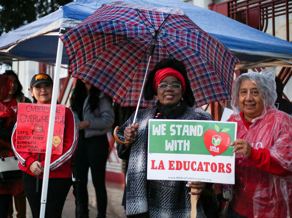"Educators from Hollenbeck Middle School in Boyle Heights, Los Angeles chant, ""Teachers united will never be defeated!"" in front of their school."