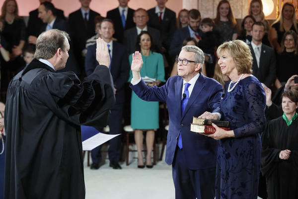 Gov. Mike DeWine takes the oath of office during his Inauguration Ceremony in the Statehouse Rotunda. The oath was administered by his son, Ohio Supreme Court Justice Pat DeWine.