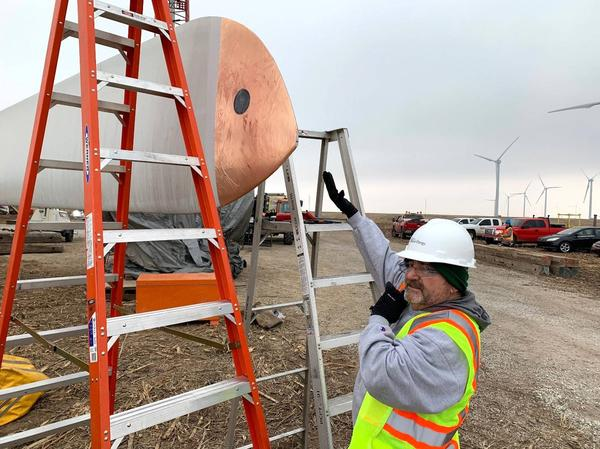WSU Environmental Test Lab director Billy Martin applies the special wrap he invented to the end of a wind turbine blade.