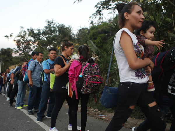 Honduran migrants wait in line to cross over the border checkpoint into Guatemala in Agua Caliente, Honduras. A new caravan of at least several hundred Hondurans has set off toward the United States on foot or in vehicles. Some have already crossed into Guatemala.