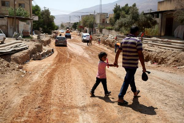 A father and his daughter cross a street under renovations as part of a U.S. aid grant in the village of al-Badhan, north of Nablus in Israeli occupied West Bank in August 2018.