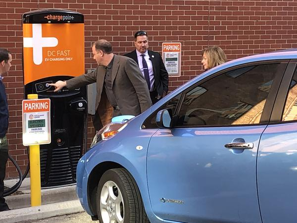 Gov. Jared Polis starts charging an electric vehicle in downtown Denver on Thursday morning. Polis signed an executive order that aims to bring more electric cars to the state.
