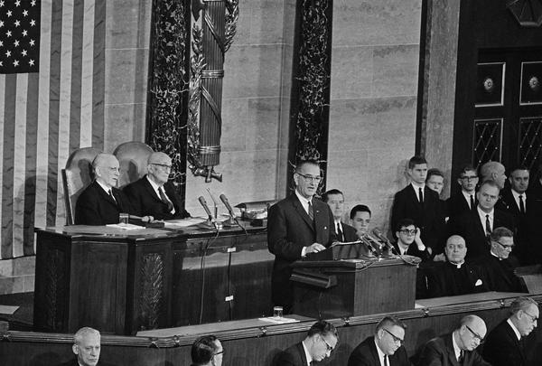 """President Lyndon B. Johnson delivers his State of the Union address to a joint session of Congress in 1964. Speaking in the House of Representatives, the chief executive said one of his aims was """"unconditional war on poverty in America."""""""