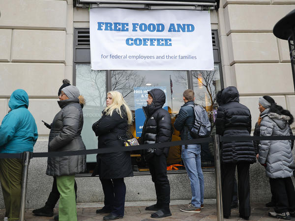 People wait in line at Chef Jose Andres' World Central Kitchen for free meals to workers affected by the government shutdown in Washington, DC.