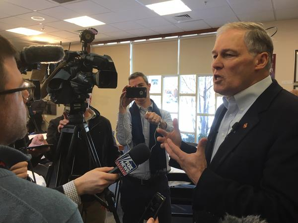 Gov. Jay Inslee speaks with reporters following a talk on climate change at the New Hampshire Institute of Politics in Manchester.