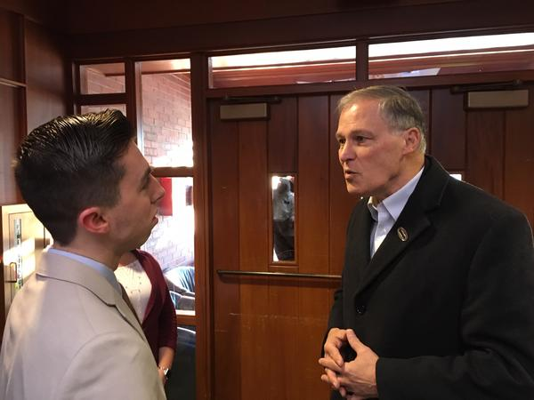 Gov. Jay Inslee speaks with Saint Anselm College sophomore Jordan Cook before speaking to students about climate change.