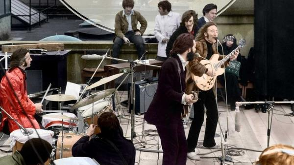In 1969, Ken Mansfield, (pictured in white in the far back) was the U.S. manager of Apple Records and one of the few people allowed on the rooftop to witness the band's final performance. He shares his memories of the historic event in his new book <em>The Roof: The Beatles' Final Concert</em>
