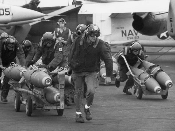 U.S. Navy armorers wheel out 500-pound bombs for the wing racks of jets aboard the aircraft carrier USS Kitty Hawk in March 1971 off the coast of Vietnam.