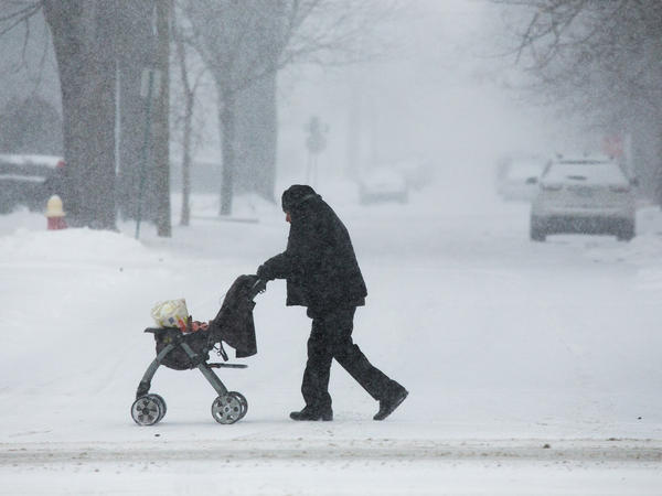 A man pushes a stroller with groceries as flurries swirl around on Woodward Avenue in Detroit on Monday. Millions of Michigan residents have been asked to turn their thermostats down to conserve energy during the Polar Vortex.