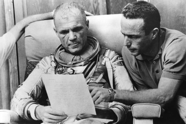 Glenn checks over notes with backup pilot Scott Carpenter after a simulated flight in 1962, prior to the Mercury-Atlas 6 mission at Cape Canaveral. The object of the mission was to put the first American spaceman into orbit around the Earth.